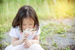 女孩嗅到的花在公园 库存照片