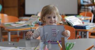 女孩图画在桌上在教室 ?? 坐在书桌的孩子 免版税图库摄影