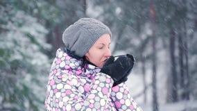 女孩在一个冷的森林或公园里站立在一个多雪的冬日 妇女游人喝从杯子的热的茶 旅游业和 股票录像