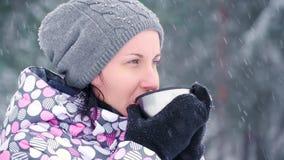 女孩在一个冷的森林或公园里站立在一个多雪的冬日 妇女游人喝从杯子的热的茶 旅游业和 影视素材