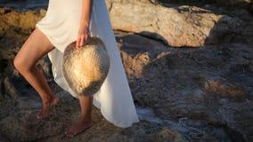 女孩在一个多岩石的海滩站立在海旁边 机体夫妇每拥抱其他零件涉及 股票录像