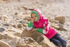 女孩在一个大岩石乏味在淡季的海边放下 图库摄影