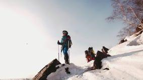 女孩在一个岩石的登山人身分在冬天,看照相机和神色下来 在背景中是她前进 股票视频
