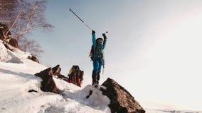 女孩在一个岩石的登山人身分在山,她举她的有滑雪杆的手对边 在背景中是a 影视素材