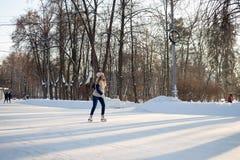 女孩在一个巨大的自由滑冰场滑冰在Sokolniki 库存照片