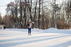 女孩在一个巨大的自由滑冰场滑冰在Sokolniki 免版税库存照片
