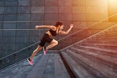女孩在一个现代台阶快速地跑 图库摄影