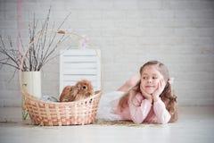 女孩在一个篮子附近说谎用兔子 免版税库存照片