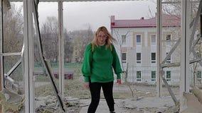 女孩在一个被放弃的被毁坏的大厦站立并且开始从它出来 影视素材