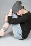女孩在一个被编织的帽子坐,拥抱他的膝盖 库存照片