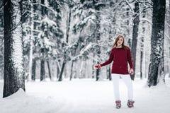 女孩在一个褐红的毛线衣和白色裤子立场穿戴了反对树干反对积雪的冬天背景  免版税库存照片