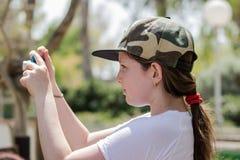 女孩在一个晴天站立并且学会拍与照相机的照片 免版税库存照片