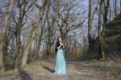女孩在一件美丽的礼服的一个森林里 图库摄影