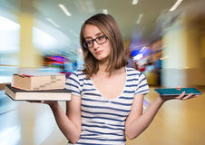 女孩在一只手和一台片剂个人计算机上的拿着一本书在地平线上方 免版税库存照片