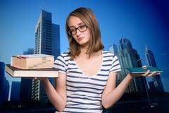 女孩在一只手和一台片剂个人计算机上的拿着一本书在地平线上方 免版税库存图片
