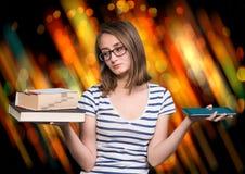 女孩在一只手和一台片剂个人计算机上的拿着一本书在ot 图库摄影