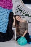 女孩在一团厚实的毛线附近坐 免版税库存照片