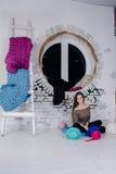 女孩在一团厚实的毛线附近坐 免版税图库摄影