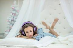 女孩在一张白色圆的床上的一个枕头说谎并且听到在耳机的音乐在有一棵新年树的卧室在圣诞前夕 免版税库存照片