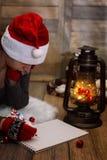 女孩在一张纸写笔圣诞节愿望 库存照片
