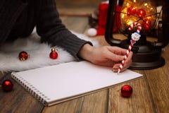 女孩在一张纸写笔圣诞节愿望 免版税库存照片