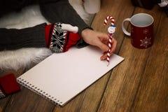 女孩在一张纸写笔圣诞节愿望 免版税图库摄影