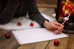 女孩在一张纸写笔圣诞节愿望 免版税库存图片