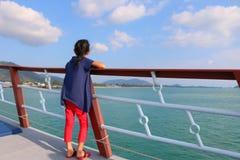 女孩在一条小船站立在海洋 免版税图库摄影