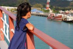 女孩在一条小船站立在海洋 免版税库存照片