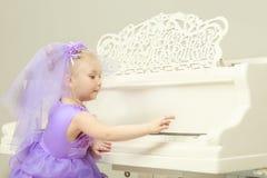 女孩在一架白色大平台钢琴使用 免版税库存照片