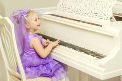 女孩在一架白色大平台钢琴使用 库存照片