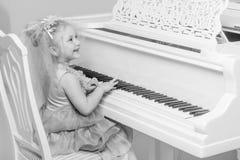 女孩在一架白色大平台钢琴使用 图库摄影