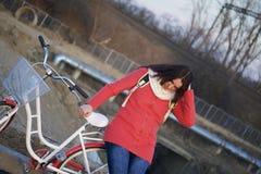 女孩在一辆停放的自行车倾斜并且调直她的头发 春天周期的基于 免版税库存图片