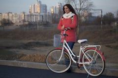 女孩在一辆停放的自行车倾斜 春天周期的基于 库存照片