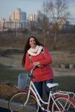 女孩在一辆停放的自行车倾斜 春天周期的基于 免版税库存图片