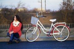 女孩在一辆停放的自行车旁边坐 春天周期的基于 免版税图库摄影