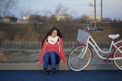 女孩在一辆停放的自行车旁边坐 春天周期的基于 免版税库存图片