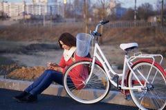 女孩在一辆停放的自行车旁边坐 观看某事在电话 春天周期的基于 免版税图库摄影