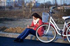 女孩在一辆停放的自行车旁边坐 观看某事在电话 春天周期的基于 库存照片