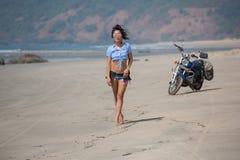 女孩在一辆摩托车的背景站立在是的 免版税库存图片