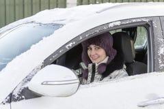 女孩在一辆白色汽车坐,当驾驶时 冬天,天 库存图片