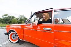 女孩在一辆老汽车的轮子后坐 免版税库存图片