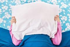 女孩在与一个枕头的床上在她的头顶部 图库摄影