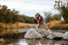 女孩在与一根钓鱼竿的秋天 免版税库存照片