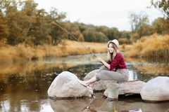 女孩在与一根钓鱼竿的秋天 图库摄影