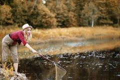 女孩在与一根钓鱼竿的秋天 库存图片