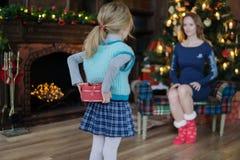 女孩在与一金黄bokeh的一棵圣诞树旁边给妈妈一件礼物 库存照片