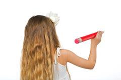 女孩在与大铅笔的发带站立  免版税库存图片
