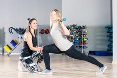 女孩在与她的个人教练员的健身房训练 库存图片