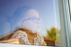 女孩在与庭院refelctions的一个窗口里 库存图片